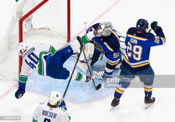 Elias Pettersson of the Vancouver Canucks trips while skating through the crease against Jordan Binnington of the St. Louis Blues during the first...
