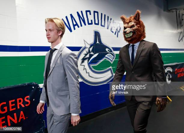 Elias Pettersson of the Vancouver Canucks walks to his dressing room beside an arena employee dressed as a wolfman before their NHL Halloween game...