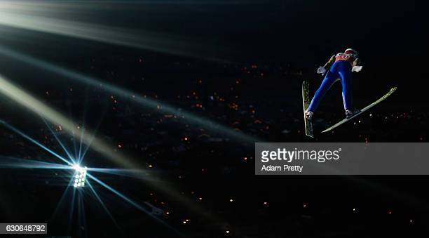 Elias Tollinger of Austria soars through the air during his qualification jump on Day 1 of the 65th Four Hills Tournament ski jumping event on...