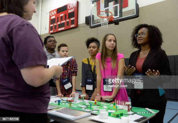 Eliazah Dixon right and fellow students from Global Village Academy West Campus present their model city 'City of Denora' to judges and visitors...