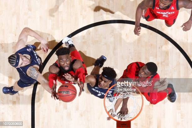 Eliel Nsoseme of the Cincinnati Bearcats battles for a rebound against Zach Hankins and Paul Scruggs of the Xavier Musketeers in the second half of...