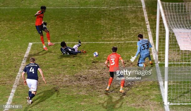 Elijah Adebayo of Luton Town scores their sides first goal past Bartosz Białkowski of Millwall whilst under pressure from Mahlon Romeo of Millwall...