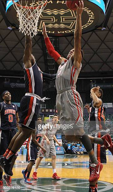 Elijah Brown of the New Mexico Lobos drives to the basket and shoots over Cinmeon Bowers of the Auburn Tigers at the Stan Sheriff Center during the...