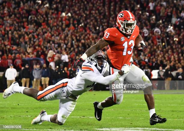 Elijah Holyfield of the Georgia Bulldogs carries the ball against Tray Bishop of the Auburn Tigers on November 10 2018 at Sanford Stadium in Athens...
