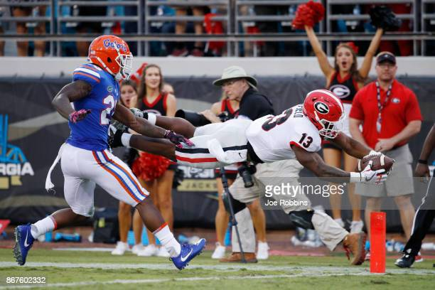 Elijah Holyfield of the Georgia Bulldogs dives into the end zone for a 39yard touchdown in the fourth quarter of a game against the Florida Gators at...