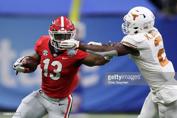 Elijah Holyfield of the Georgia Bulldogs is tackled by Kris Boyd of the Texas Longhorns during the Allstate Sugar Bowl at MercedesBenz Superdome on...