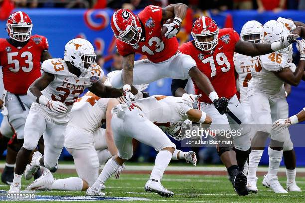 Elijah Holyfield of the Georgia Bulldogs leaps over Brandon Jones of the Texas Longhorns during the second half of the Allstate Sugar Bowl at the...
