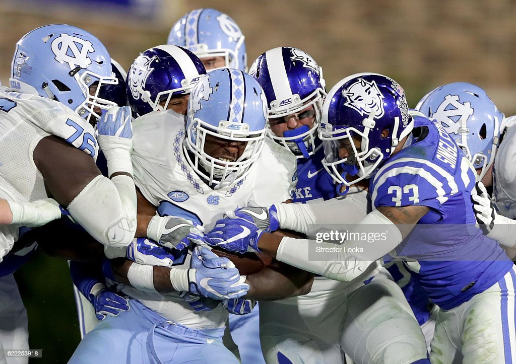Elijah Hood #34 of the North Carolina Tar Heels is stopped by the defense of the Duke Blue Devils during their game at Wallace Wade Stadium on November 10, 2016 in Durham, North Carolina.