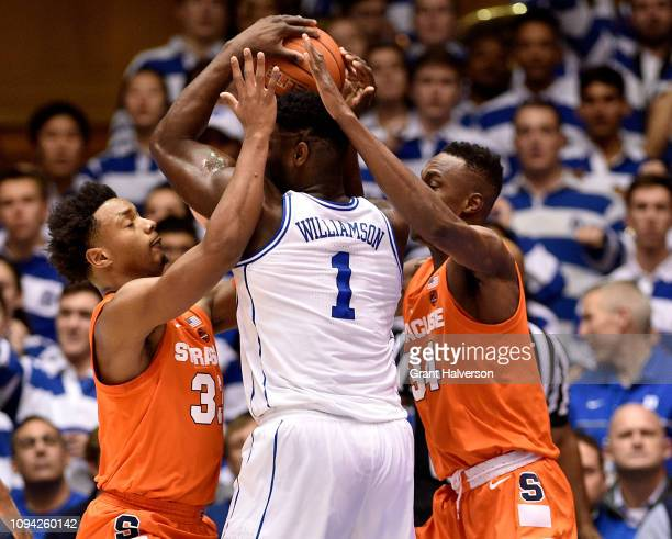Elijah Hughes and Bourama Sidibe of the Syracuse Orange defend Zion Williamson of the Duke Blue Devils during the first half of their game at Cameron...