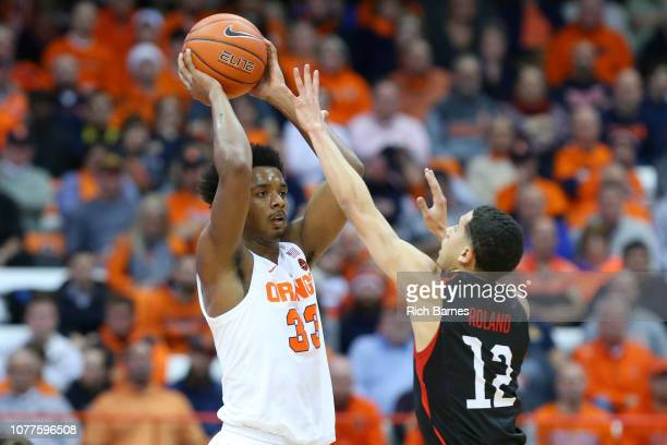 Elijah Hughes of the Syracuse Orange controls the ball as Jordan Roland of the Northeastern Huskies defends during the first half at the Carrier Dome...