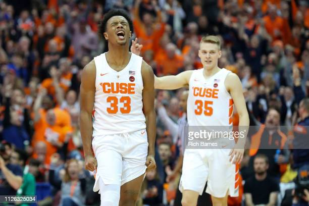 Elijah Hughes of the Syracuse Orange reacts to a made threepoint basket as teammate Buddy Boeheim gestures against the Louisville Cardinals during...