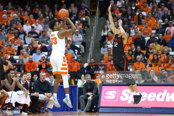 Elijah Hughes of the Syracuse Orange shoots the ball against the defense of Jordan Roland of the Northeastern Huskies during the first half at the...