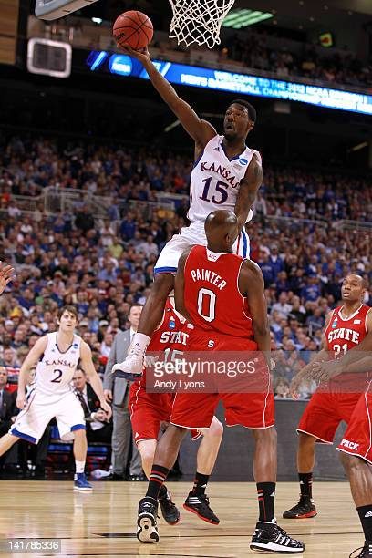 Elijah Johnson of the Kansas Jayhawks drives for a shot attempt in the first half against DeShawn Painter of the North Carolina State Wolfpack during...