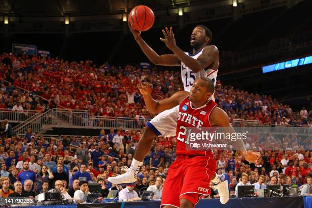 Elijah Johnson of the Kansas Jayhawks drives for a shot attempt in the second half against CJ Williams of the North Carolina State Wolfpack during...