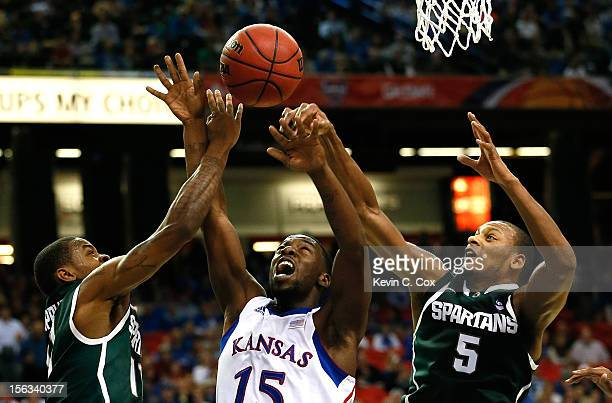 Elijah Johnson of the Kansas Jayhawks has the ball stripped by Keith Appling and Adreian Payne of the Michigan State Spartans during the 2012 State...