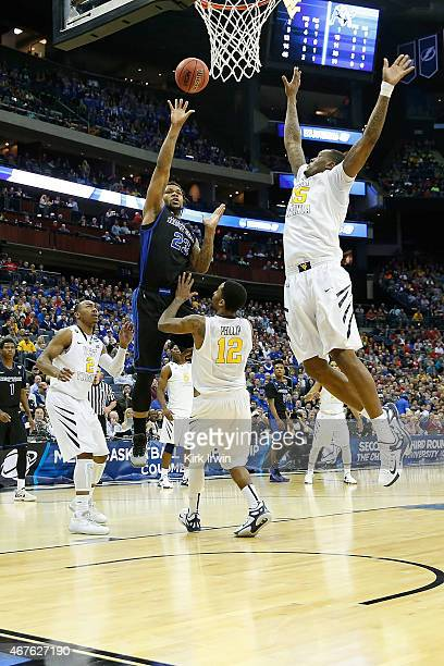 Elijah Macon of the West Virginia Mountaineers attempts to block a shot by Justin Moss of the Buffalo Bulls during the second round of the 2015 NCAA...