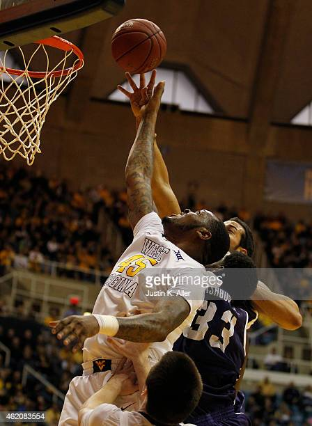 Elijah Macon of the West Virginia Mountaineers attempts to secure a rebound against Chris Washburn of the TCU Horned Frogs during the game at the WVU...