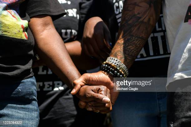 Elijah McClain's mother Sheneen McClain left holds the hand of a protester as they rally outside the Aurora Police Department Headquarters to demand...