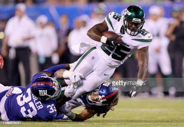 Elijah McGuire of the New York Jets carries the ball as Kenny Ladler and Josiah Tauaefa of the New York Giants defend in the fourth quarter during a...
