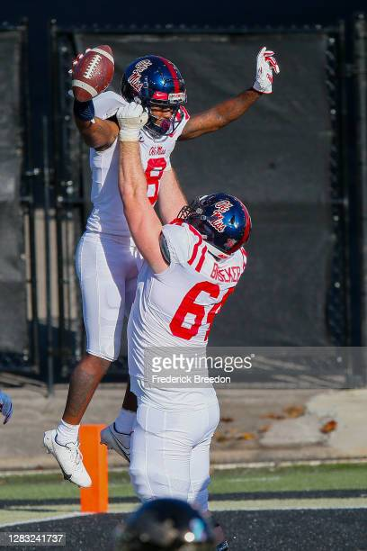 Elijah Moore of the Mississippi Rebels is congratulated by teammate Nick Broeker after scoring a touchdown against the Vanderbilt Commodores during...