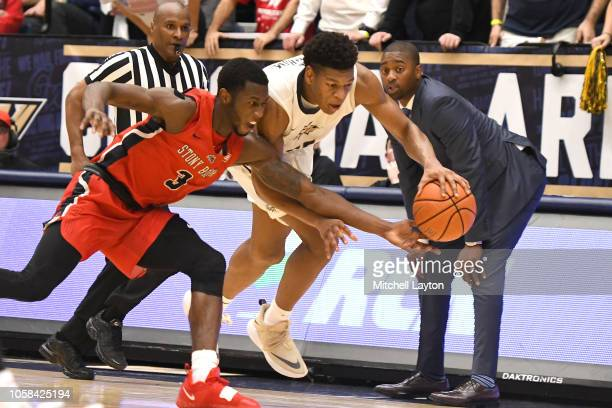 Elijah Olaniyi of the Stony Brook Seawolves and Mezie Offurum of the George Washington Colonials fight for a loose ball during a college basketball...