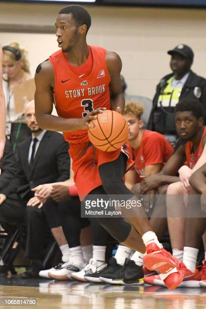 Elijah Olaniyi of the Stony Brook Seawolves looks to pass the ball during a college basketball game against the George Washington Colonials at the...