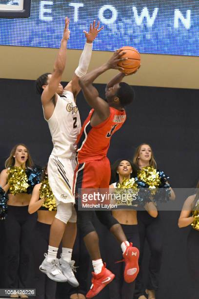 Elijah Olaniyi of the Stony Brook Seawolves takes a shot over Armel Potter of the George Washington Colonials during a college basketball game at the...
