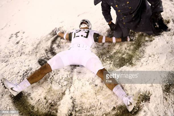 Elijah Riley of the Army Black Knights makes a snow angel after the win over the Navy Midshipmen on December 9 2017 at Lincoln Financial Field in...