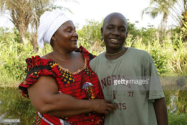 Elijah Rufus poses on May 29 2013 with his aunt Karpo Moiseemah at his home in the Zubah Town area of Monrovia Liberia where he is recovering from...
