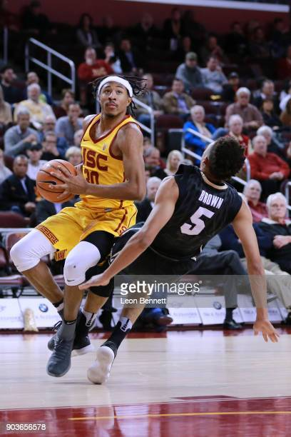 Elijah Stewart of the USC Trojans handles the ball against Deleon Brown of the Colorado Buffaloes during a PAC12 basketball game at Galen Center on...