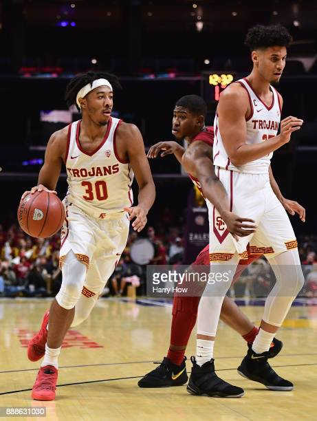 Elijah Stewart of the USC Trojans uses a screen from Bennie Boatwright on Christian James of the Oklahoma Sooners during the Basketball Hall of Fame...