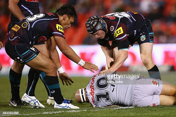 Elijah Taylor and Nigel Plum of the Panthers show concern for Sam Rapira of the Warriors after he was injured in a heavy tackle during the round 23...