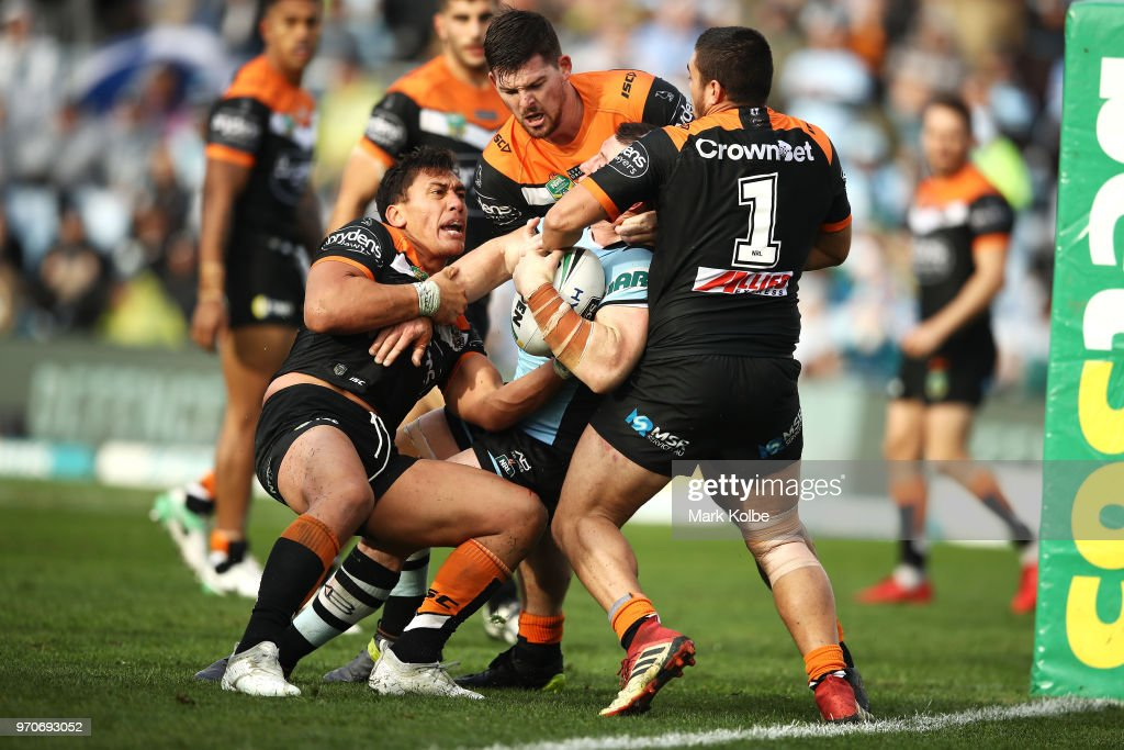 Elijah Taylor, Matt Eisenhuth and Tuimoala Lolohea of the Tigers attempt to tackle Paul Gallen of the Sharks before he scores try during the round 14 NRL match between the Cronulla Sharks and the Wests Tigers at Southern Cross Group Stadium on June 10, 2018 in Sydney, Australia.