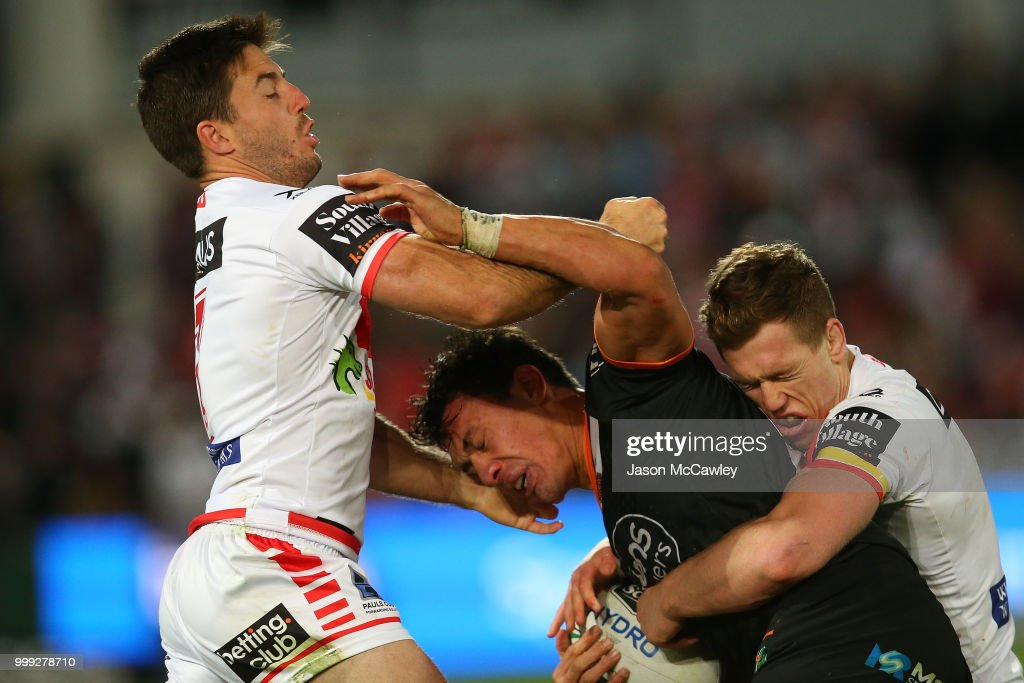 Elijah Taylor of the Tigers is tackled by Ben Hunt and Cameron McInnes of the Dragons during the round 18 NRL match between the St George Illawarra Dragons and the Wests Tigers at UOW Jubilee Oval on July 15, 2018 in Sydney, Australia.