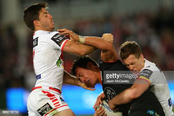 Elijah Taylor of the Tigers is tackled by Ben Hunt and Cameron McInnes of the Dragons during the round 18 NRL match between the St George Illawarra...