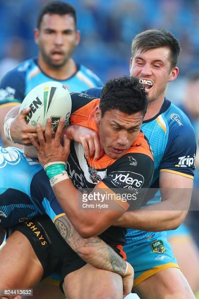 Elijah Taylor of the Tigers is tackled during the round 21 NRL match between the Gold Coast Titans and the Wests Tigers at Cbus Super Stadium on July...