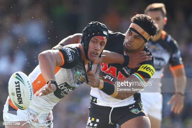 Elijah Taylor of the Tigers is tackled during the round two NRL match between the Wests Tigers and the Penrith Panthers at Campbelltown Sports...