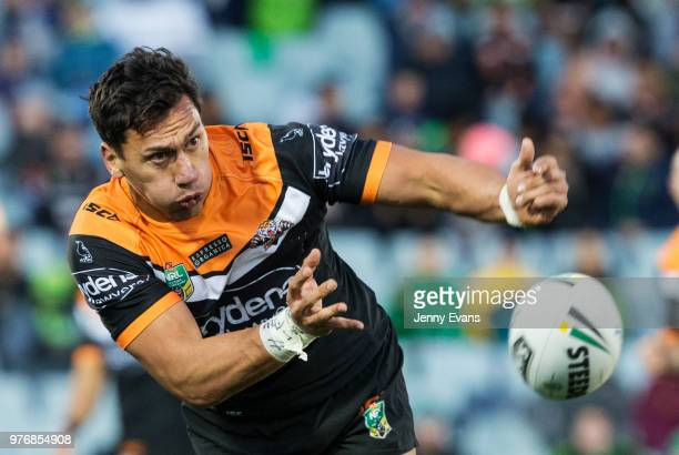 Elijah Taylor of the Tigers passes the ball during the round 15 NRL match between the Wests Tigers and the Canberra Raiders at Campbelltown Sports...
