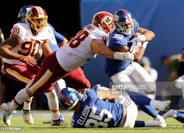 Elijhaa Penny of the New York Giants carries the ball as Matthew Ioannidis of the Washington Redskins defends at MetLife Stadium on September 29,...
