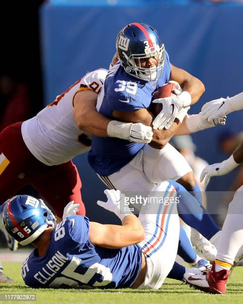 Elijhaa Penny of the New York Giants carries the ball as Matthew Ioannidis of the Washington Redskins defends in the fourth quarter at MetLife...