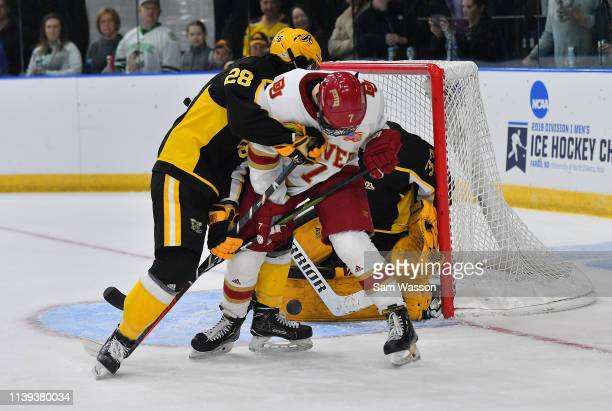 Elijiah Barriga of the American International Yellow Jackets and Brett Stapley of the Denver Pioneers battle for the puck in front of the net during...