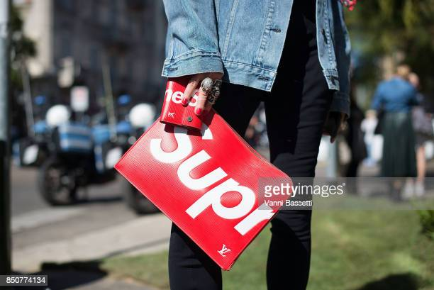 Elina Halimi poses wearing a denim jacket and Louis Vuitton x Supreme clutch after the Fendi show during Milan Fashion Week Spring/Summer 2018 on...