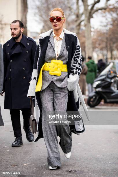 Elina Halimi wearing a Celine long coat grey suit big yellow belt and grey Hermes bag is seen in the streets of Paris before the Issey Miyake Men...