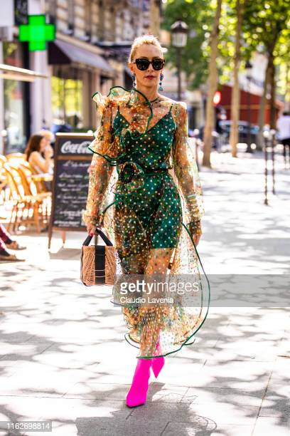 Elina Halimi, wearing a green decorated dress with sheer details, hot pink heels and straw bag, is seen outside Zuhair Murad show during Paris...