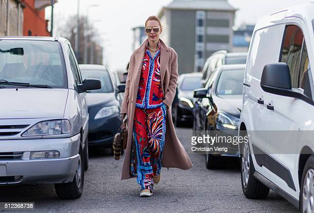 Elina Halimi wearing a printed Emilio Pucci pajama suit and a rose Celine wool coat and Dior shoes seen outside Emilio Pucci during Milan Fashion...