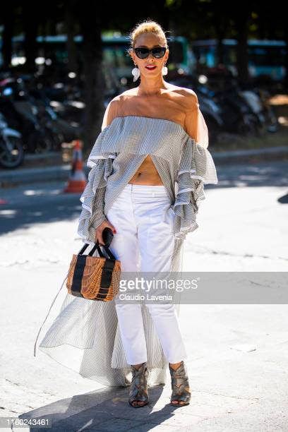 Elina Halimi wearing a striped long top white pants grey heels and straw bag is seen outside Alexandre Vauthier show during Paris Fashion Week Haute...