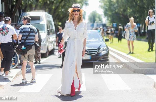 Elina Halimi wearing a white dress straw hat red boots is seen outside Armani during Milan Men's Fashion Week Spring/Summer 2018 on June 19 2017 in...