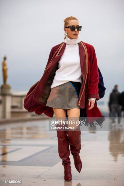 Elina Halimi wearing a white jumper brown and black mini skirt burgundy boots burgundy coat and scarf is seen outside Elie Saab show during Paris...