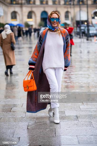 Elina Halimi wearing a white jumper white pants white boots colorful long cardigan printed hair scarf and neon orange bag is seen outside Alexis...
