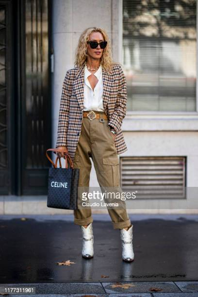 Elina Halimi wearing a white shirt checked blazer beige pants snake print boots and Celine bag is seen outside the Faith Connexion show during Paris...